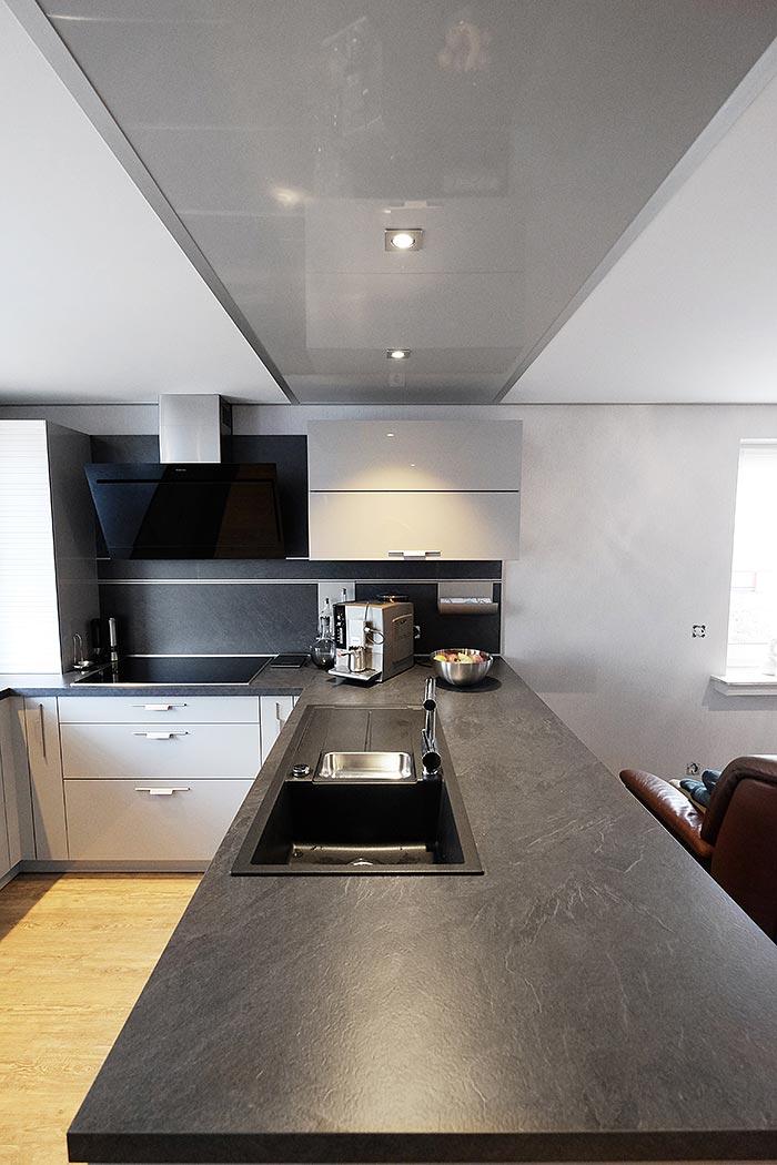 Kücheninsel mit LED-Beleuchtung und Hochglanz-Element in Szene gesetzt