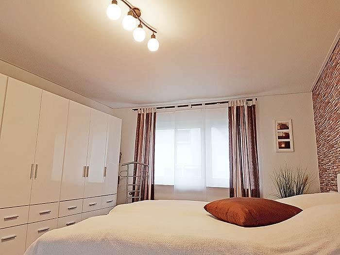 Schöne, glatte Schlafzimmerdecke in Siegen. Als Beleuchtung dient die Unterbauleuchte.