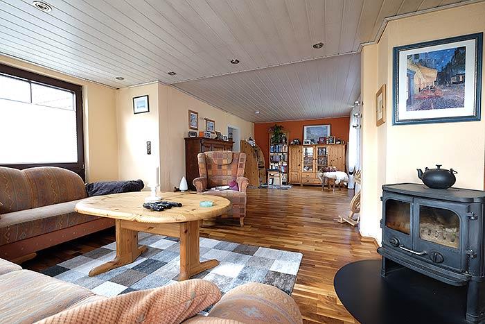 Das Wohnzimmer mit Ofen und großer Fläche sollte auch auf eine Deckenhöhe gebracht werden.