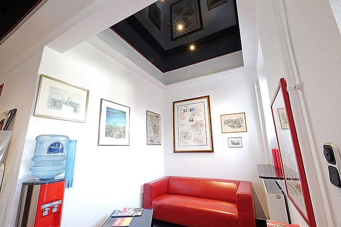 Besucher erleben die schwarze Decke mit roten Zierleisten - passend zum Design der Firma BMD