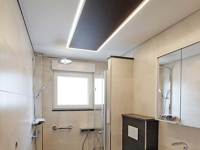 PLAMECO Badezimmerdecke in Erndtebrück mit LED-Lichtkanal und abgesetztem Element in der Mitte.