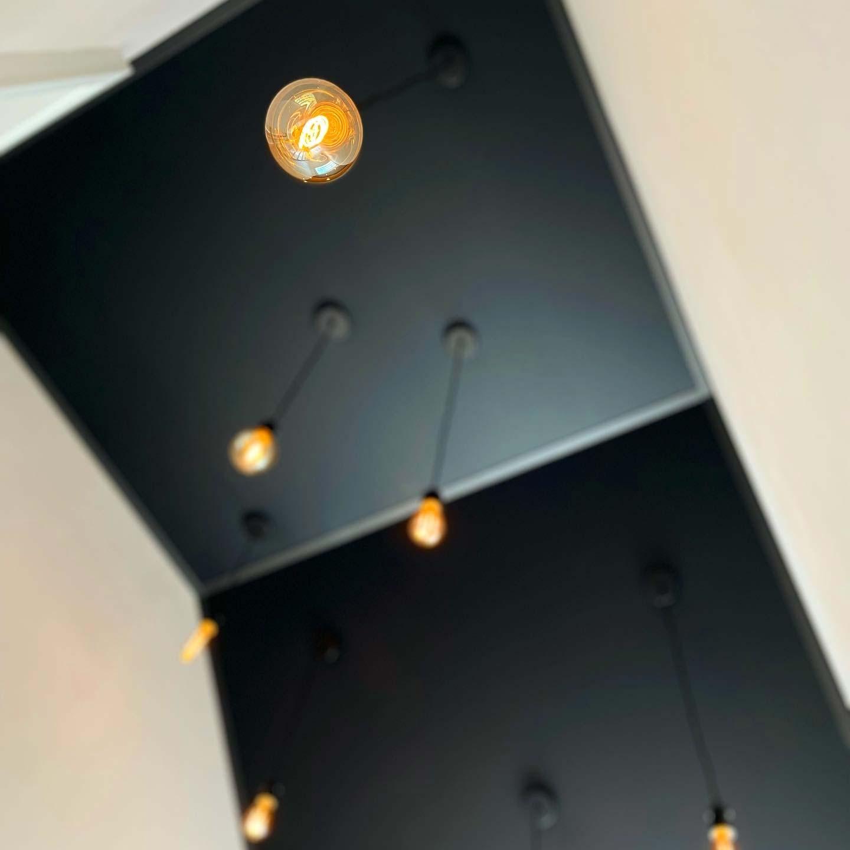 Filament LED-Leuchten mit Textilkabel passend zur schwarz-matten Decke im Treppenhaus
